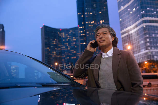 Smiling mature asian man standing beside car and talking by smartphone — Stock Photo