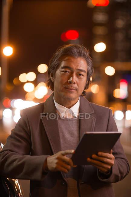 Sério maduro asiático homem segurando digital tablet e olhando para câmera no noite cidade — Fotografia de Stock