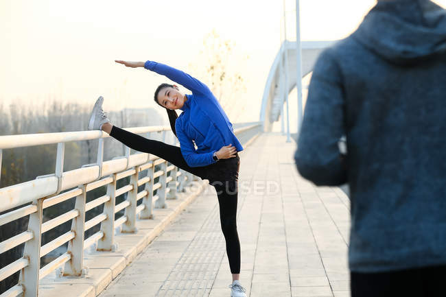 Cropped shot of man running and sporty young woman stretching on bridge — Stock Photo