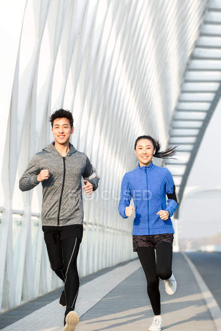 Front view of young asian athletes in sportswear running and smiling at camera on bridge — Stock Photo