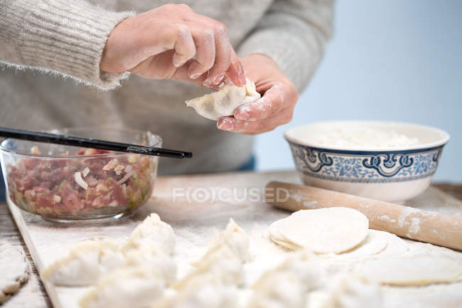 Cropped shot of person preparing traditional chinese dumplings — Stock Photo