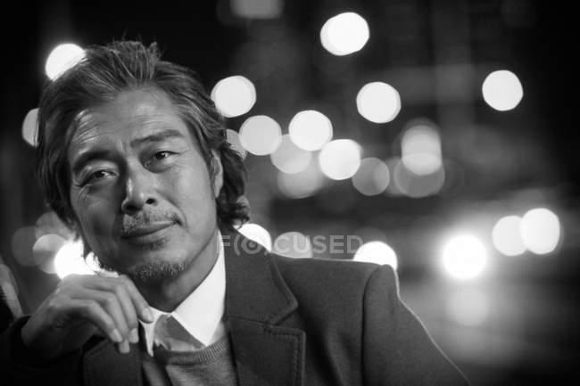Портрет красивого зрелого азиатского мужчину, смотрящего в камеру в ночном городе, черно-белое изображение — стоковое фото