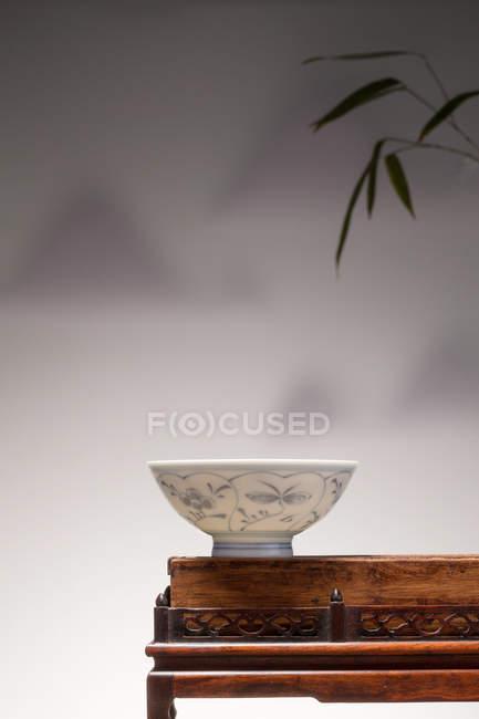 Nahaufnahme der chinesischen Keramikschale auf einem Holztisch und Bambusblättern auf grauem Hintergrund — Stockfoto