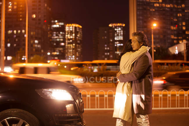 Felice coppia asiatica che si abbraccia sulla strada alla sera — Foto stock