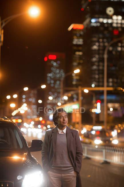 Maturo asiatico uomo in piedi con le mani in tasche accanto auto e guardando lontano in notte città — Foto stock
