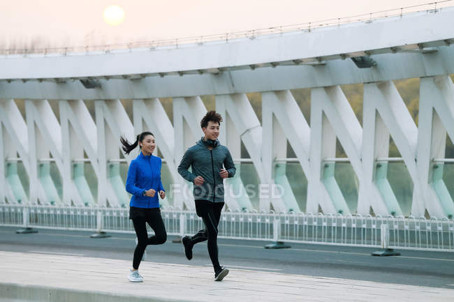 Smiling young asian man and woman in sportswear running together on bridge — Stock Photo