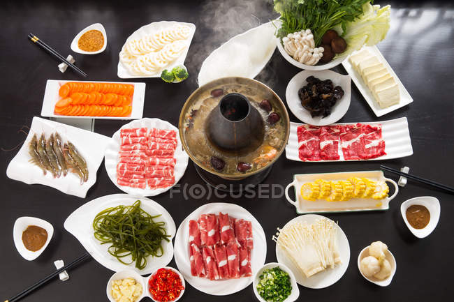 Top view of various ingredients, meat, vegetables, seafood and copper hot pot, chafing dish concept — Stock Photo