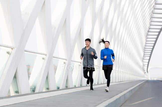 Sonrientes jóvenes corredores masculinos y femeninos corriendo juntos en el puente moderno - foto de stock