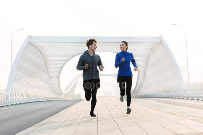 Full length view of happy sporty young asian couple smiling each other and running together on bridge — Stock Photo