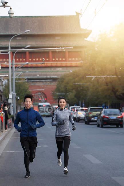 Улыбающиеся молодые спортсмены и спортсмены, бегущие вместе по улице — стоковое фото
