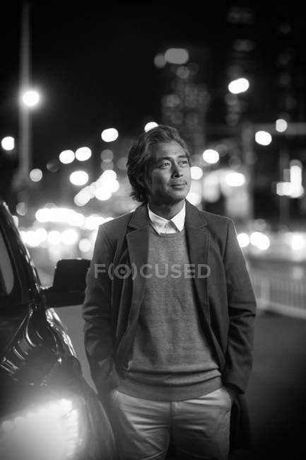 Preto e branco foto de pensive maduro ásia homem de pé perto de carro e olhando para longe no noite cidade — Fotografia de Stock