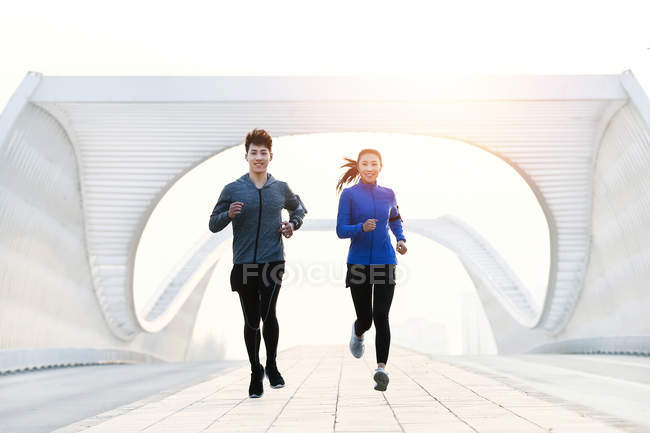 Young asian male and female athletes in sportswear jogging together on modern bridge — Stock Photo