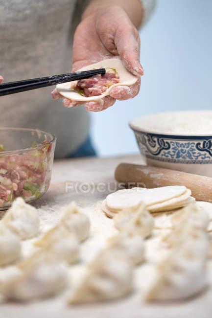 Coup recadré de la personne préparant les boulettes chinoises traditionnelles — Photo de stock