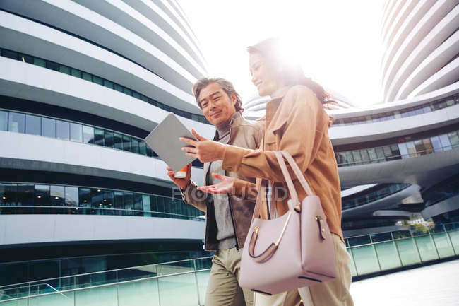 Cheerful businesspeople walking and using tablet near modern business center — Stock Photo