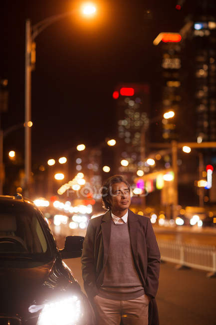 Mature asian man standing beside car and looking away in night city — Stock Photo