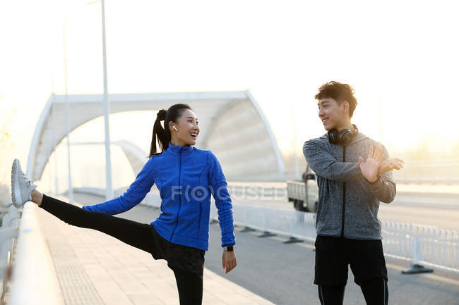 Happy young asian couple in sportswear smiling each other and stretching together on bridge in the morning — Stock Photo