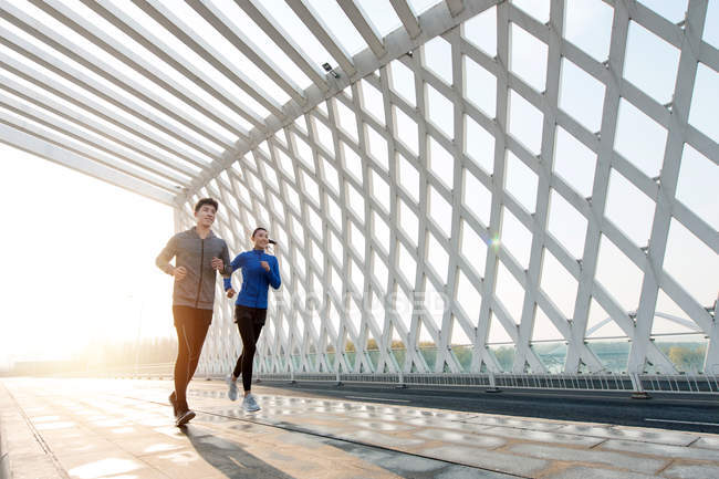 Low angle view of smiling young asian athletes running together on modern bridge — Stock Photo