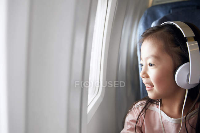Adorável criança feliz em fones de ouvido sentado no avião e olhando para a janela — Fotografia de Stock
