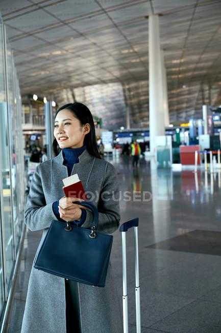 Bella giovane donna d'affari in possesso di passaporto e biglietto nel salone dell'aeroporto — Foto stock