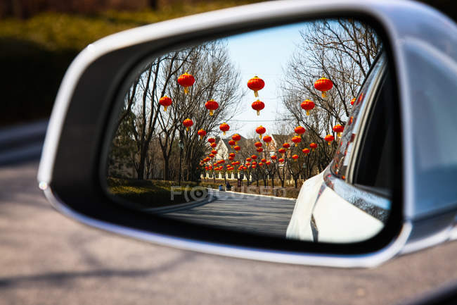 Auto rear view mirror with red lanterns reflection — Stock Photo