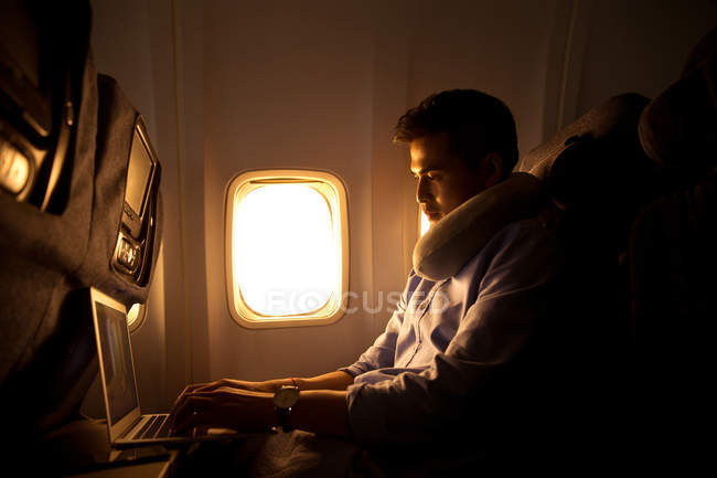 Young man using laptop while sitting in plane, side view — Stock Photo