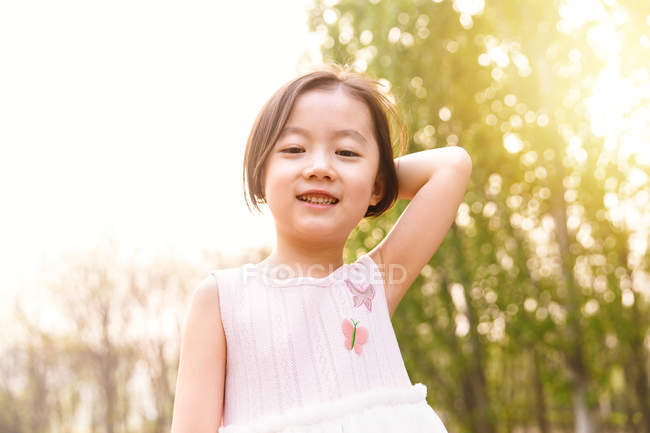 Portrait of adorable asian kid looking at camera outdoors — Stock Photo