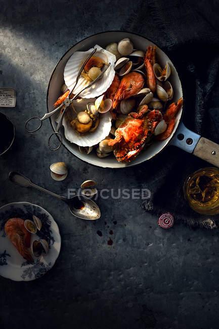 Vue de dessus de divers fruits de mer délicieux dans la poêle sur surface grise — Photo de stock