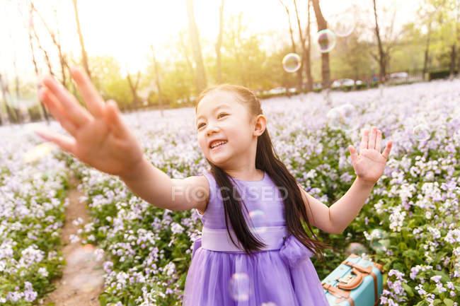 Adorable asiatique enfant dans robe attraper savon bulles à fleur champ — Photo de stock