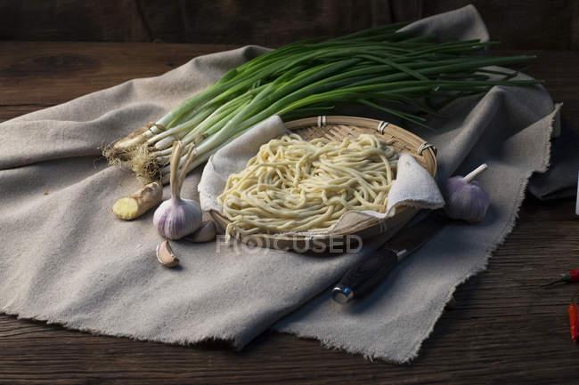 Nahaufnahme von frischen gesunden Zutaten, Nudeln, Zwiebeln und Knoblauch mit Messer auf Holztisch — Stockfoto