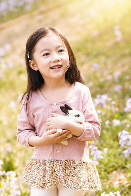 Adorable asiático niño en vestido holding conejo en flor campo - foto de stock