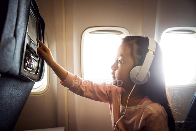 Side view of cute little girl in headphones traveling by plane — Stock Photo