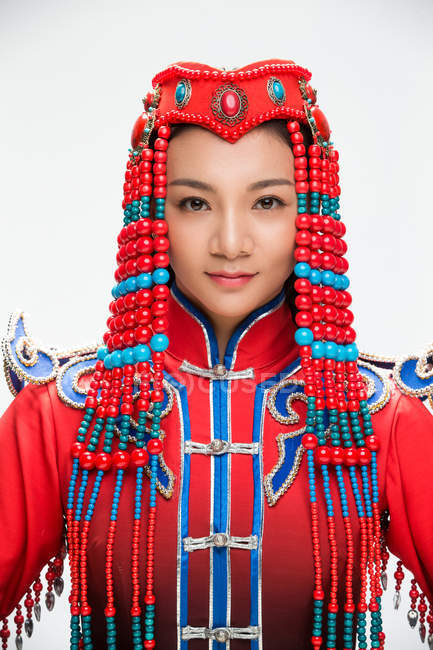 Beautiful young woman in the Mongolian costume looking at camera — Stock Photo