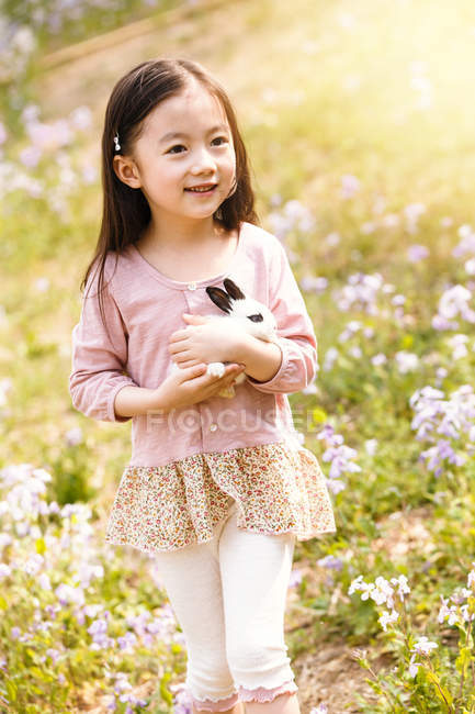 Adorable asian kid in dress holding rabbit at flower field — Stock Photo