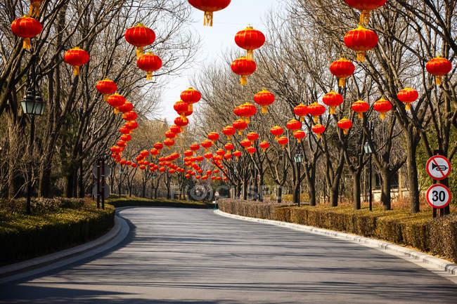 Традиционные красные китайские фонари висят над дорогой — стоковое фото