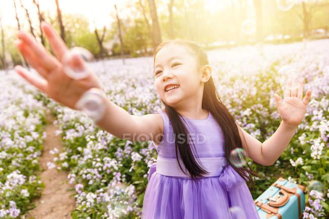 Чарівні азіатські хлопець у сукні лову мильні бульбашки в полі квітки — стокове фото
