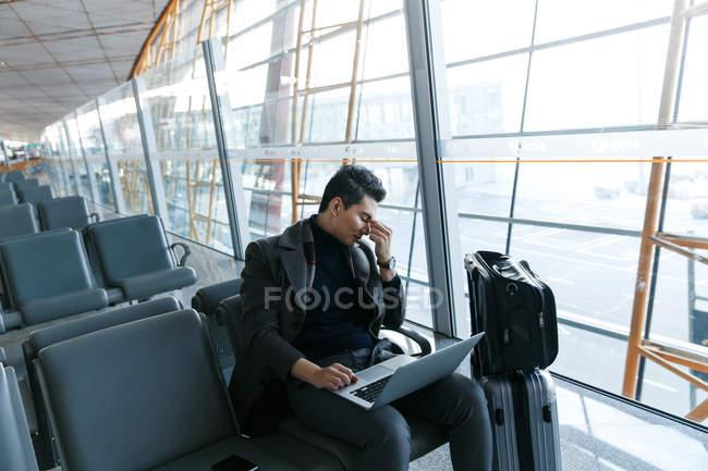 Jeune homme d'affaires assis et utilisant un ordinateur portable à l'aéroport — Photo de stock