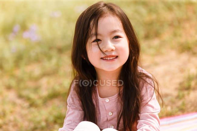 Портрет очаровательного улыбающегося азиатского ребенка, смотрящего на улицу — стоковое фото