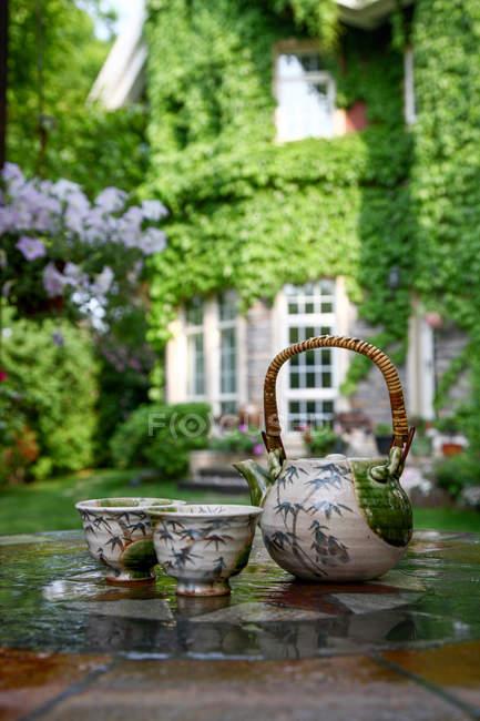 Nahaufnahme von Keramik-Tee-Set mit Wasserkocher und Tassen auf dem Tisch im Hinterhof — Stockfoto
