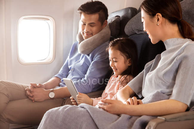 Щаслива родина з одною дитиною подорожує літаком і користується цифровим планшетом. — стокове фото