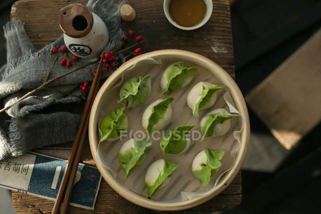 Draufsicht auf köstliche traditionelle chinesische Knödel in Schüssel auf dem Tisch — Stockfoto