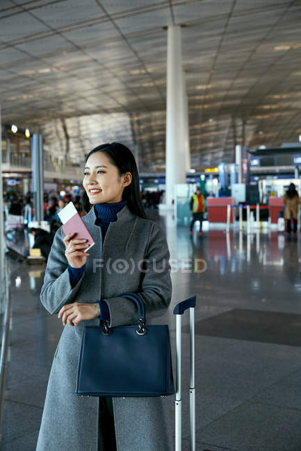 Beautiful young businesswoman holding passport and ticket in airport lounge — Stock Photo