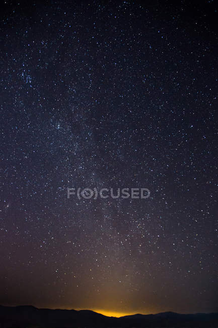 Low angle view of majestic starry sky above dark hills — Stock Photo