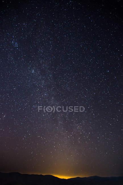 Visão de ângulo baixo do majestoso céu estrelado acima de colinas escuras — Fotografia de Stock