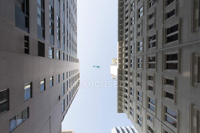 Снизу вид на городскую архитектуру Гонконга и голубое небо — стоковое фото
