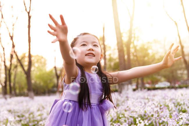 Adorável asiático criança no vestido captura sabão bolhas no flor campo — Fotografia de Stock