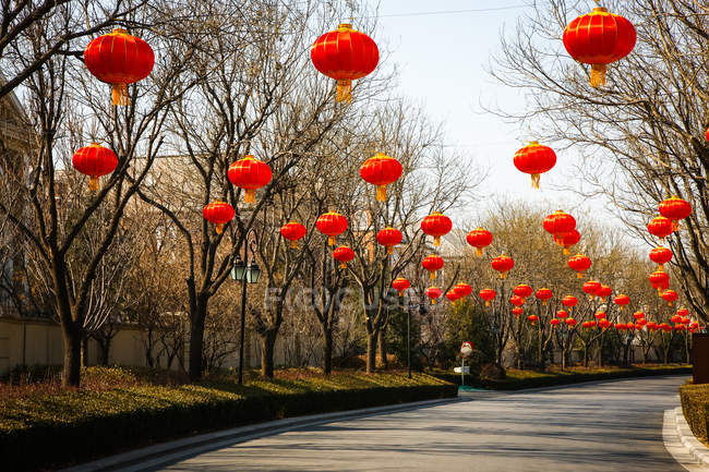 Faroles chinos rojos tradicionales colgando por encima de la carretera - foto de stock