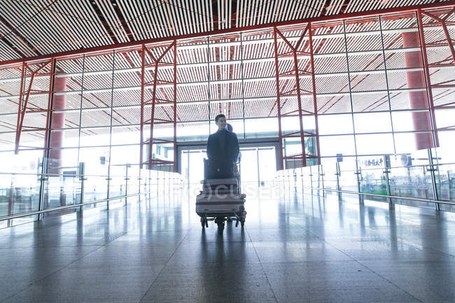 Young businessman with luggage at the airport, low angle view — Stock Photo