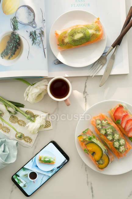 Top view of delicious healthy breakfast and smartphone on white table — Stock Photo