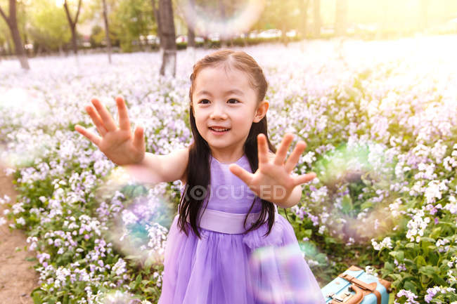 Adorable asian kid in dress catching soap bubbles at flower field — Stock Photo