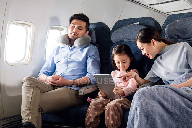 Happy family with one child traveling by plane, father sleeping and mother with daughter using digital tablet — Stock Photo